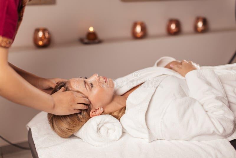 Doutor que faz massagens os templos de uma mulher imagem de stock royalty free