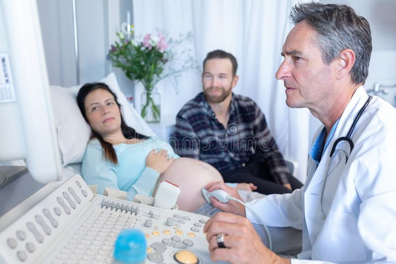 Doutor que faz a varredura do ultrassom para a mulher gravida no hospital imagem de stock royalty free