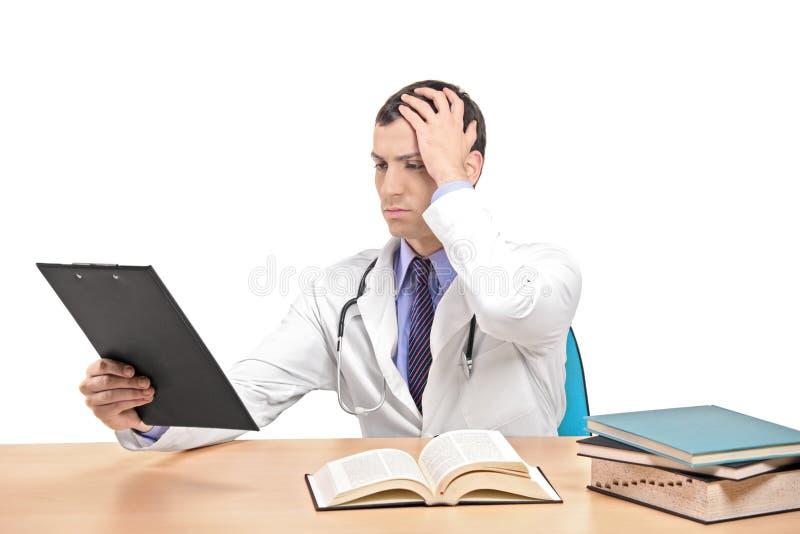 Doutor que golpeia sua cabeça que realiza um erro fotos de stock