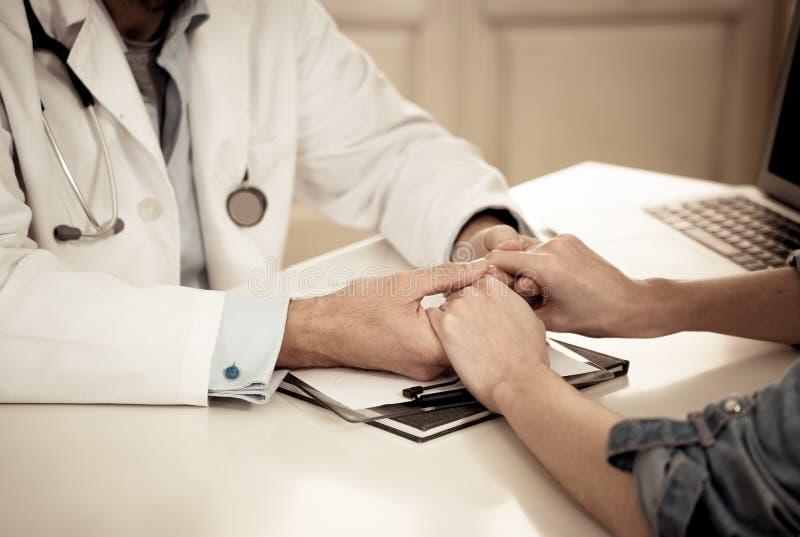 Doutor que guarda as mãos pacientes fêmeas com piedade e conforto para o incentivo e a empatia imagem de stock