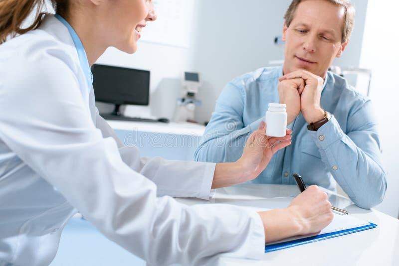 doutor que guarda a garrafa dos comprimidos que escrevem o diagnóstico e que falam com paciente maduro fotografia de stock royalty free