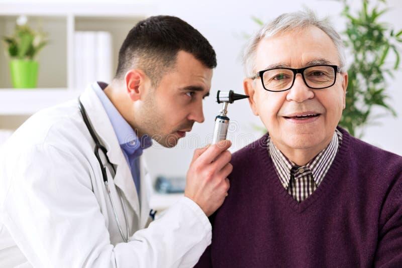 Doutor que guarda o otoscope e que examina a orelha paciente foto de stock royalty free