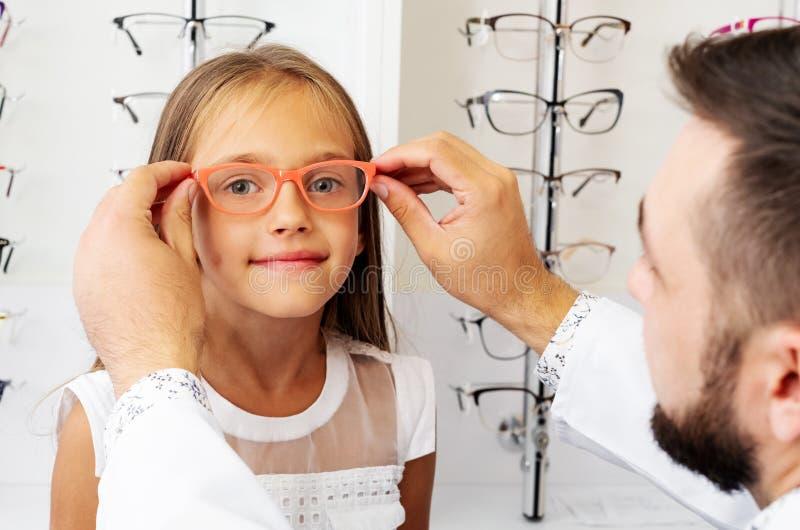 Doutor que guarda vidros alaranjados na menina imagens de stock royalty free