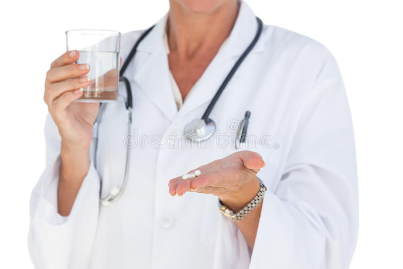 Doutor que guardara para fora comprimidos e vidro de água imagem de stock