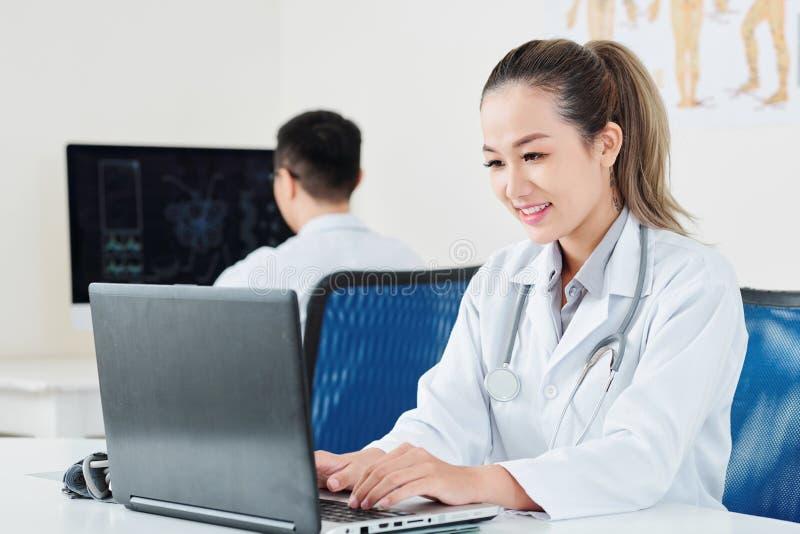 Doutor que incorpora a informação paciente fotografia de stock