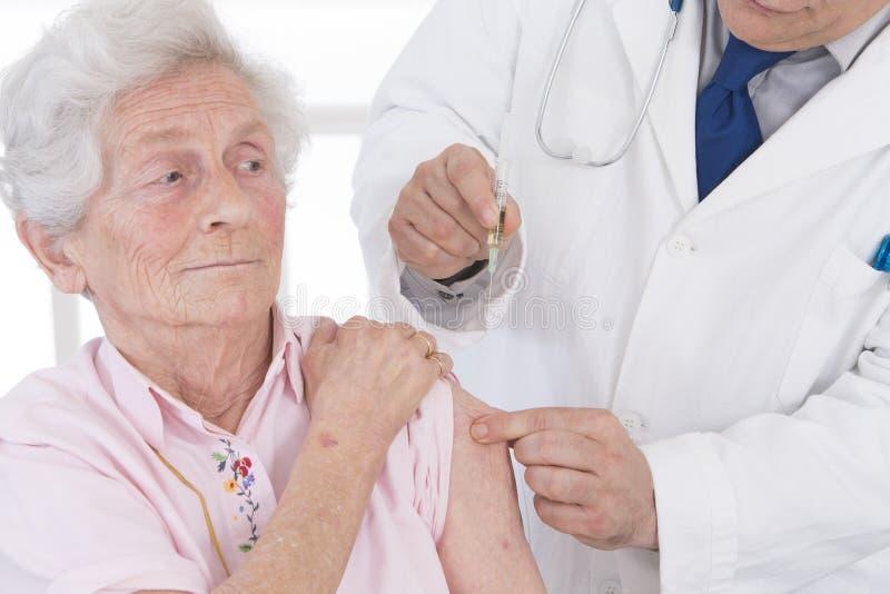 Doutor que injeta a vacina à mulher superior imagens de stock