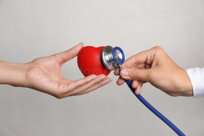 Doutor que mantém o estetoscópio perto do coração do brinquedo - na mão do paciente contra o fundo cinzento, close up foto de stock royalty free