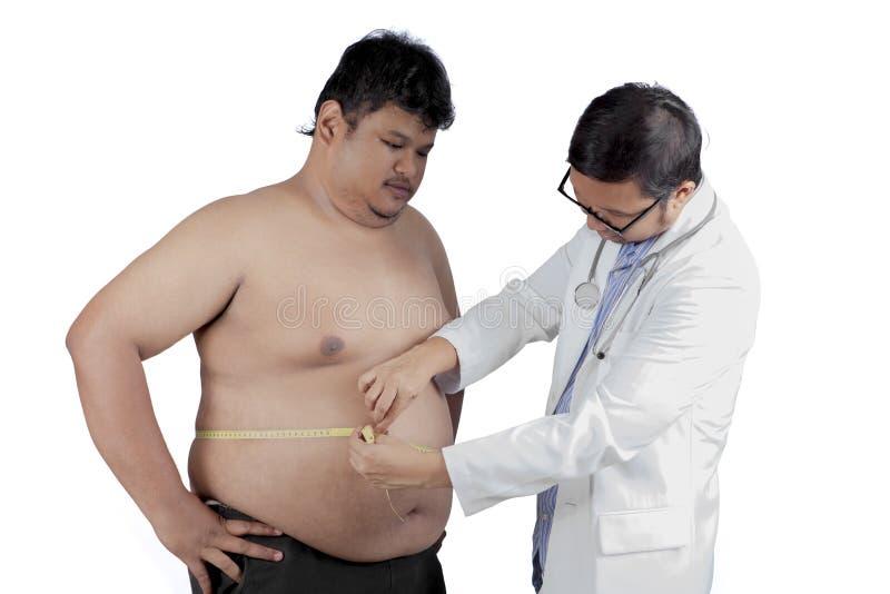 Doutor que mede o paciente excesso de peso fotos de stock royalty free
