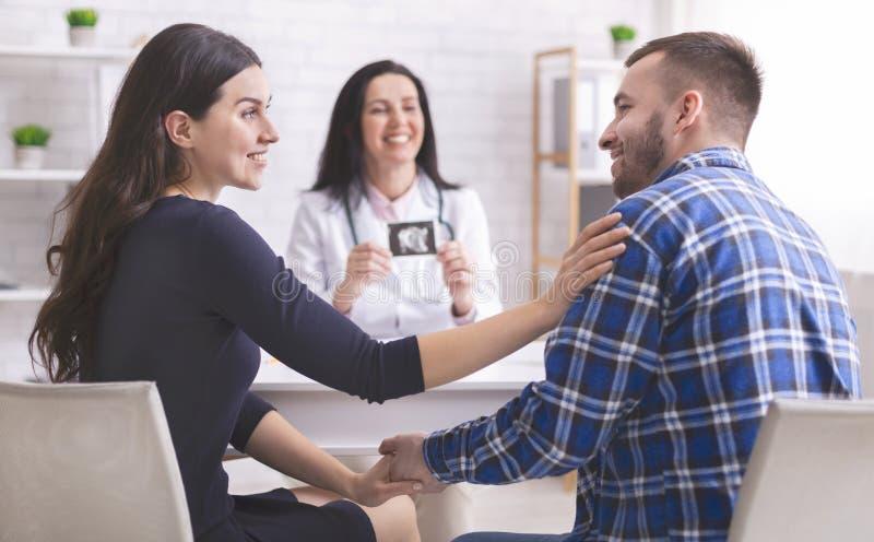 Doutor que mostra a imagem do ultrassom aos pares felizes novos imagens de stock royalty free