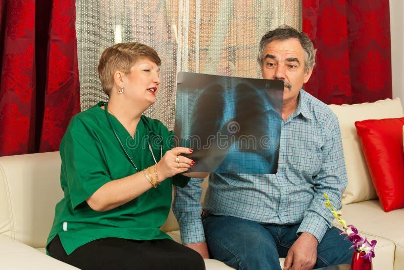Doutor que mostra o raio X ao macho paciente imagens de stock