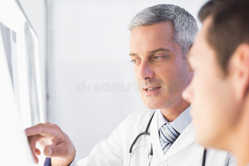 Doutor que mostra raios de X a seu paciente foto de stock