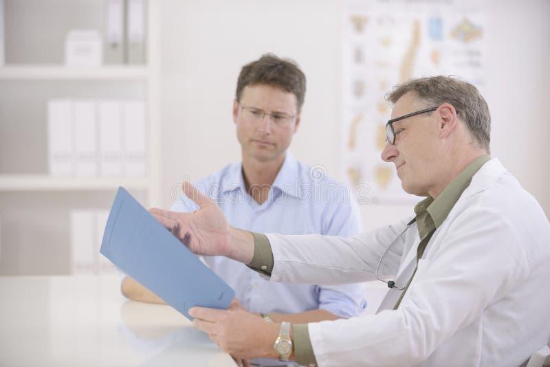 Doutor que mostra resultados ao paciente fotografia de stock