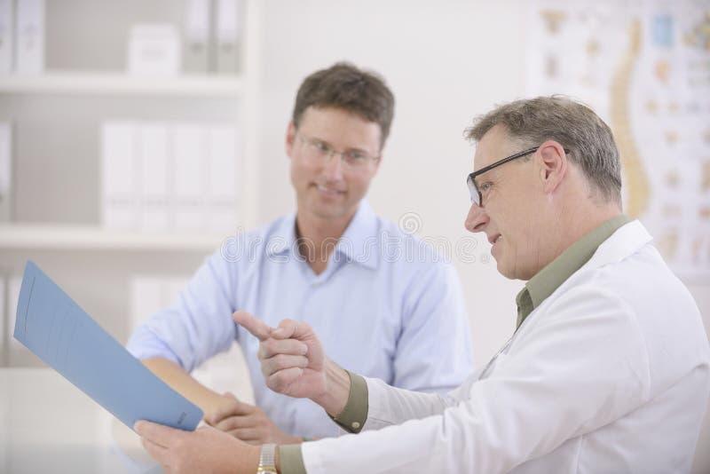 Doutor que mostra resultados ao paciente imagens de stock