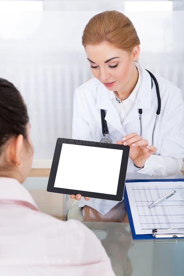 Doutor que mostra a tabuleta digital ao paciente fotos de stock