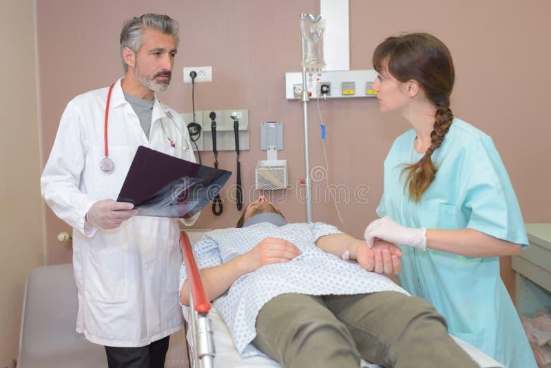 Doutor que ocupa do paciente com enfermeira imagens de stock