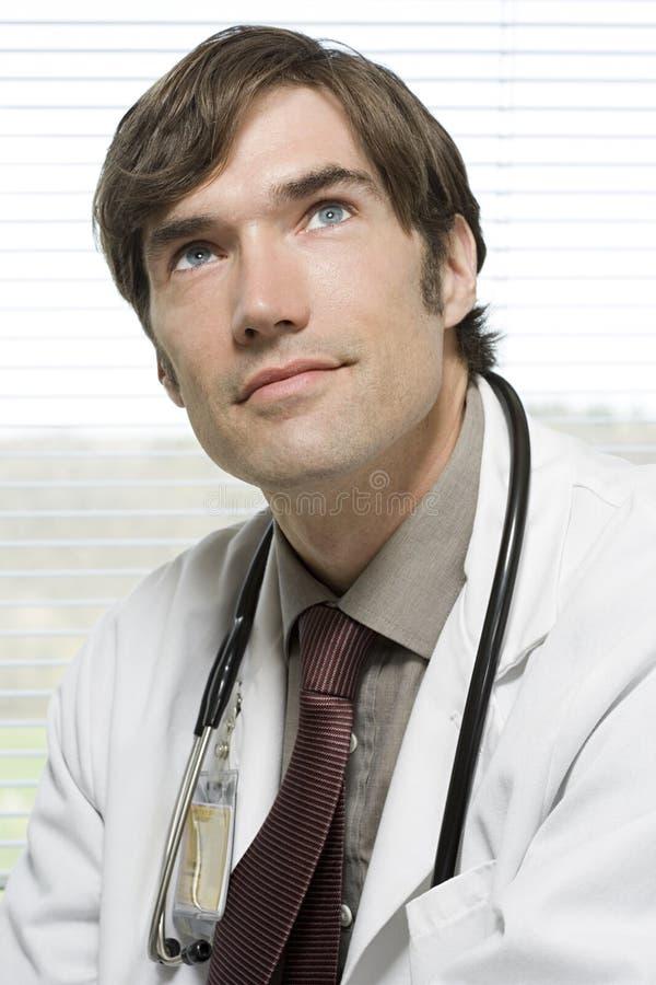 Doutor que olha acima imagem de stock