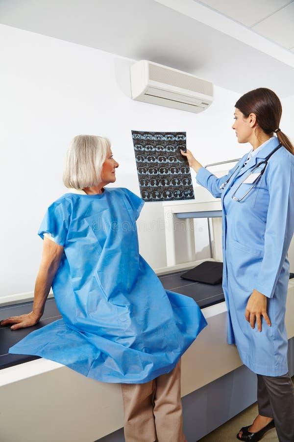 Doutor que olha imagens do raio X do sênior fotografia de stock royalty free