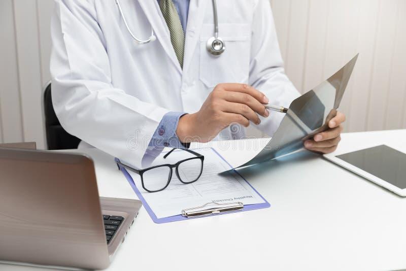 Doutor que olha o filme de raio X principal no escritório imagens de stock royalty free