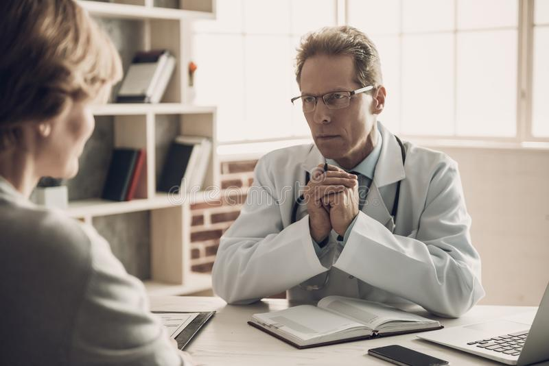 Doutor que olha o paciente com expressão séria foto de stock royalty free