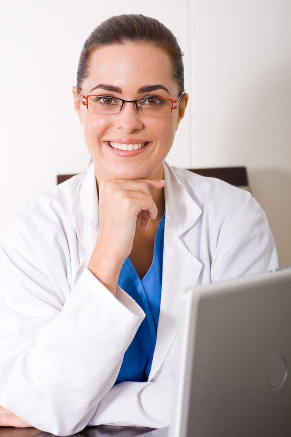 Doutor que senta-se pelo portátil fotografia de stock royalty free