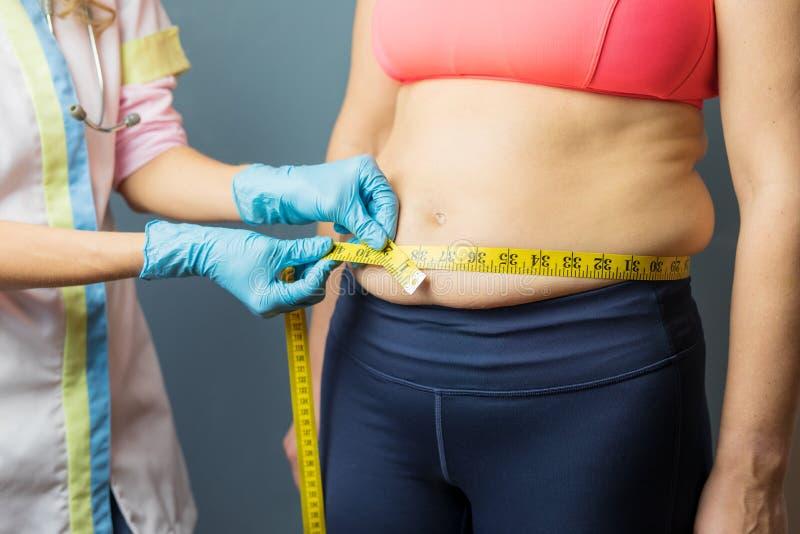 Doutor que toma medidas obesos da gordura corporal do paciente foto de stock