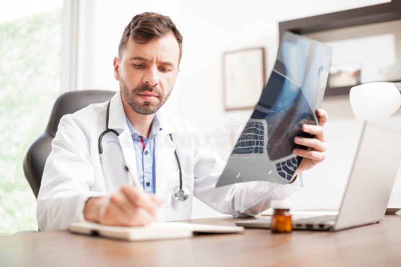 Doutor que toma notas de alguns raios X imagem de stock
