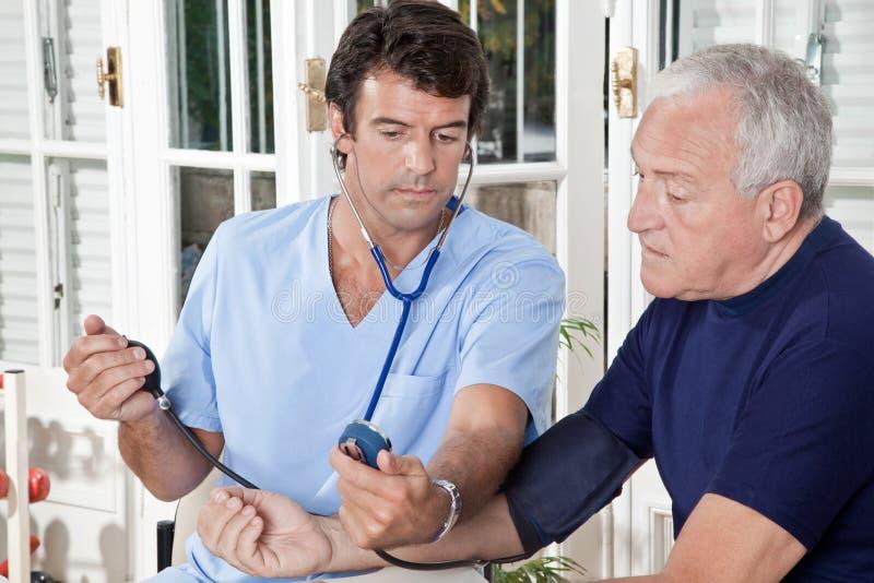Doutor que toma a pressão sanguínea imagem de stock