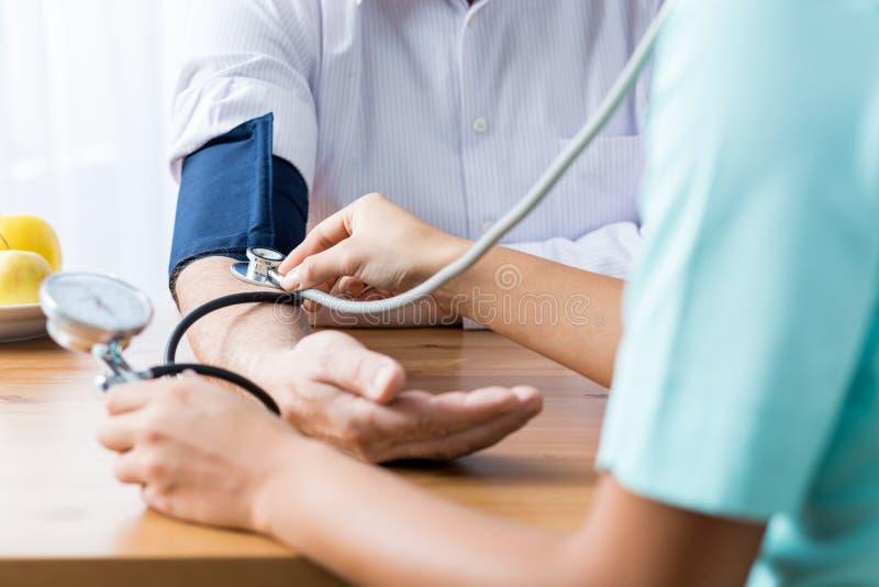 Doutor que toma a pressão sanguínea fotos de stock royalty free