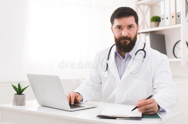 Doutor que trabalha com o laptop no escritório imagens de stock royalty free