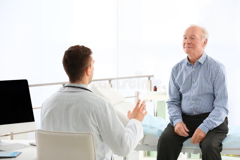 Doutor que trabalha com paciente idoso foto de stock