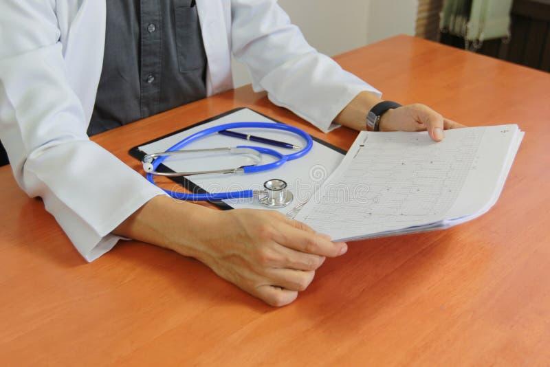 Doutor que trabalha no hospital e que verifica os resultados eletrocardiograma e estetoscópio no papel na prancheta, cuidados méd imagens de stock