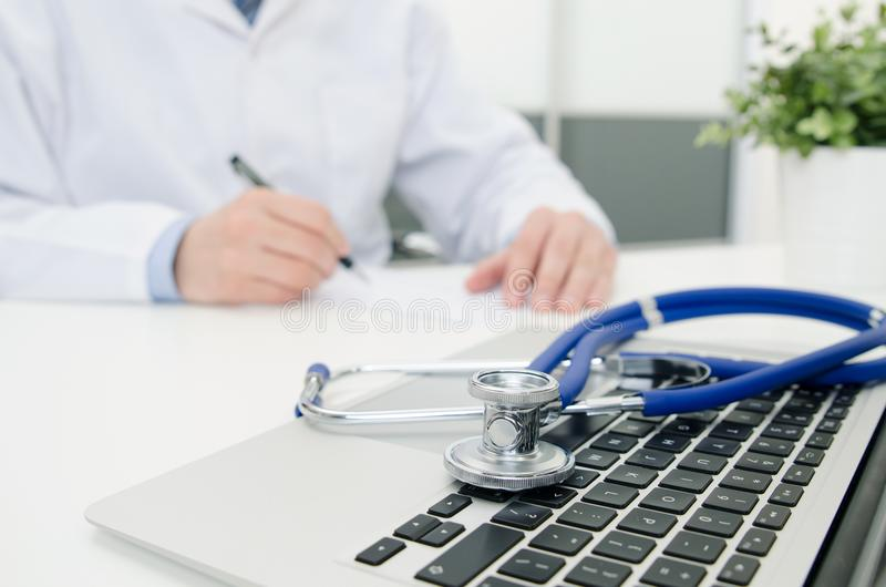 Doutor que trabalha no hospital Estetoscópio no teclado do portátil fotografia de stock