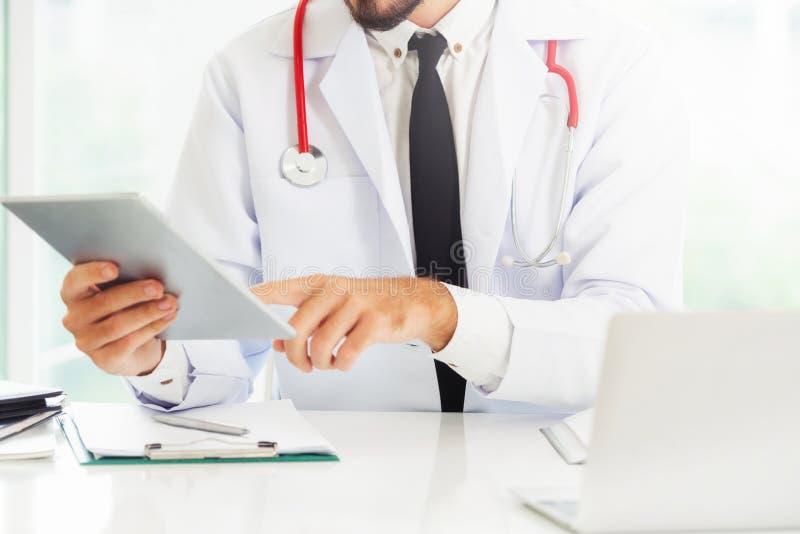 Doutor que trabalha no tablet pc no hospital foto de stock