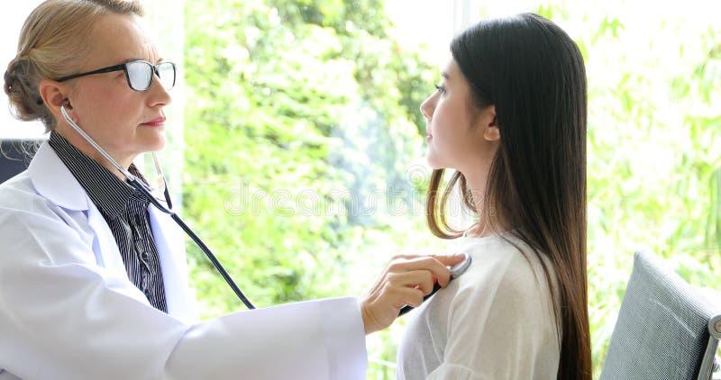 Doutor que usa o estetoscópio para o paciente de exame em seu escritório em hospitais foto de stock royalty free