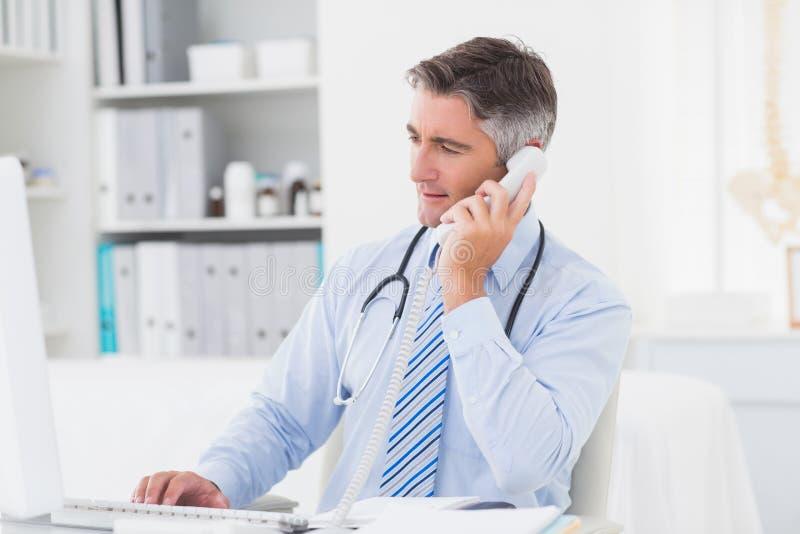 Doutor que usa o telefone ao trabalhar no computador imagens de stock royalty free