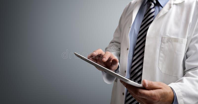 Doutor que usa a tabuleta digital imagem de stock