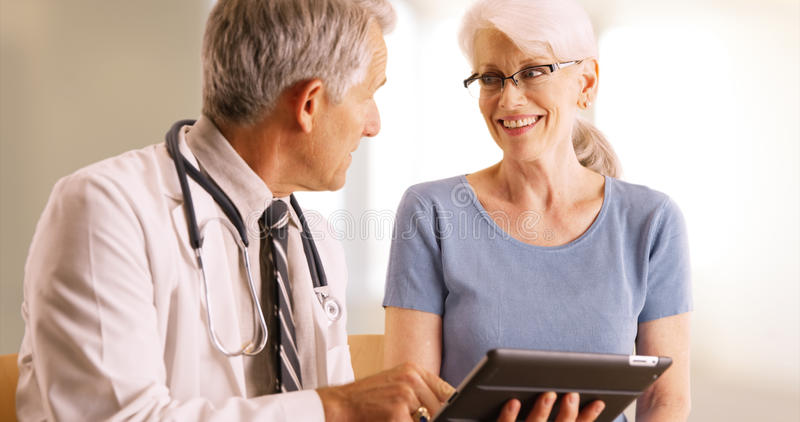 Doutor que vai sobre o arquivo idoso da saúde do ` s da mulher no escritório com tabuleta imagens de stock royalty free
