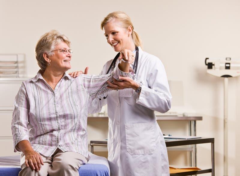 Doutor que verific o braço sênior da mulher fotografia de stock royalty free