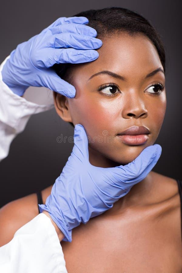 Doutor que verifica a cara africana da menina fotos de stock royalty free