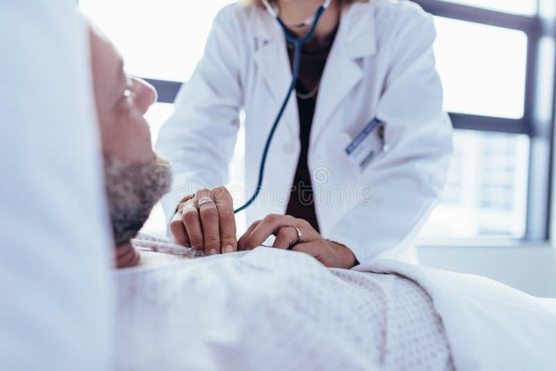 doutor que verifica a frequência cardíaca paciente imagens de stock