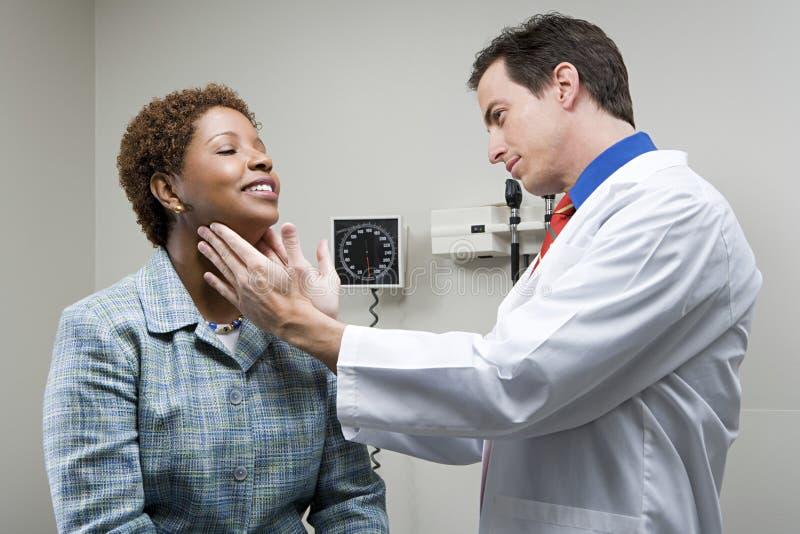 Doutor que verifica a garganta da mulher imagem de stock royalty free