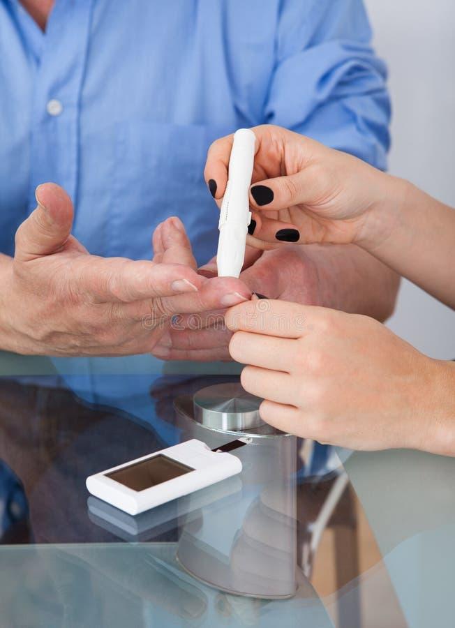 Doutor que verifica o nível da glicose no paciente do diabético imagem de stock royalty free