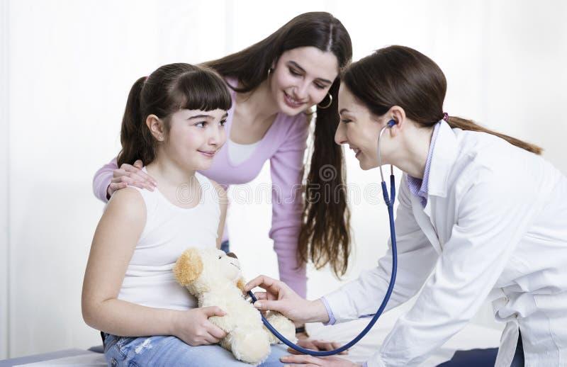 Doutor que visita uma menina bonito e que joga com ela foto de stock