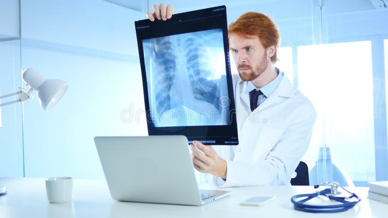 Doutor sério Checking Raio X do paciente para o diagnóstico imagens de stock