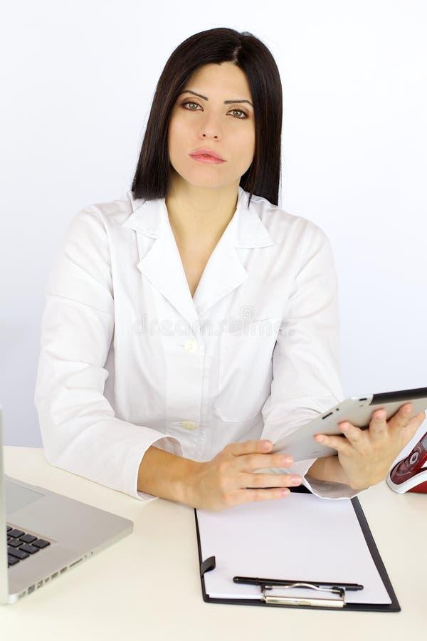 Doutor sério da mulher que trabalha com a tecnologia que senta-se na mesa imagem de stock