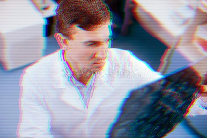 Doutor sério que olha de sobrancelhas franzidas e nos resultados do MRT fotografia de stock