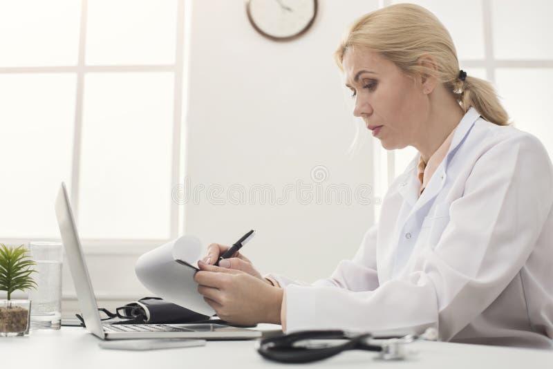 Doutor sério que toma notas no local de trabalho fotos de stock royalty free