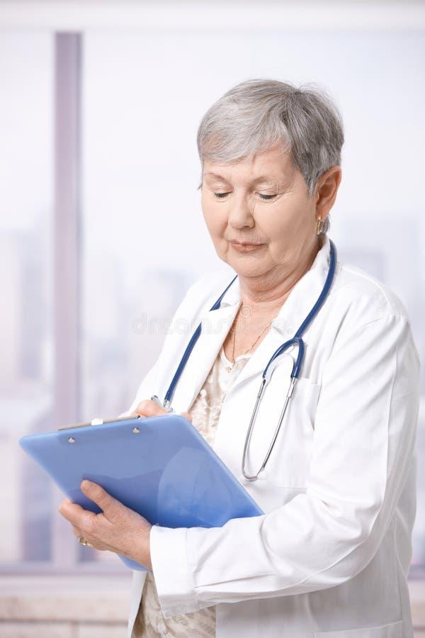 Doutor sênior que toma notas fotografia de stock