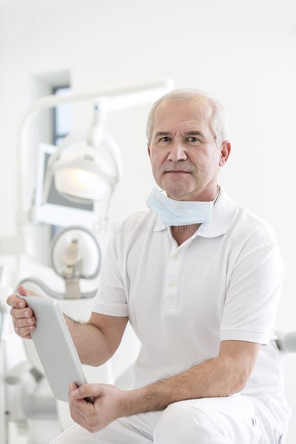 Doutor seguro que guarda a tabuleta digital na clínica dental fotos de stock