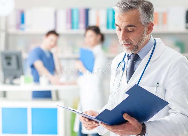 Doutor seguro que verifica informes médicos imagem de stock